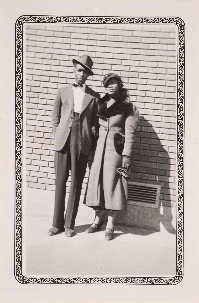 a man in a suit and hat and a woman in a coat in front of a brick wall
