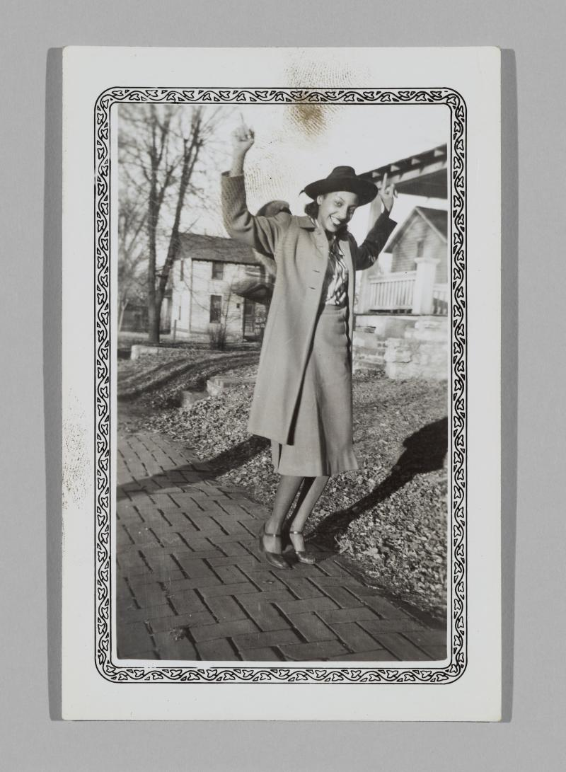 a woman in a coat and hat poses playfully on a sidewalk with her arms in the air
