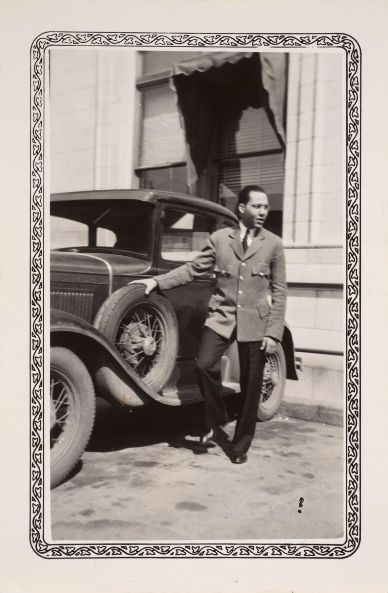 a man in a suit poses near a car