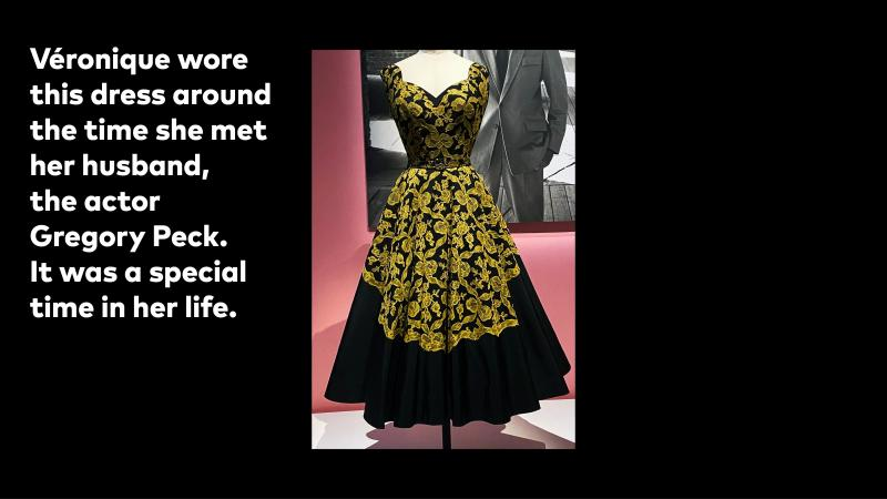 Sleeveless, tea length dress made of black silk with a yellow lace overlay.