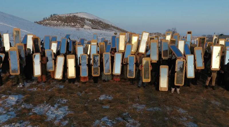 Dozens of people holding up mirrors on a mountainside