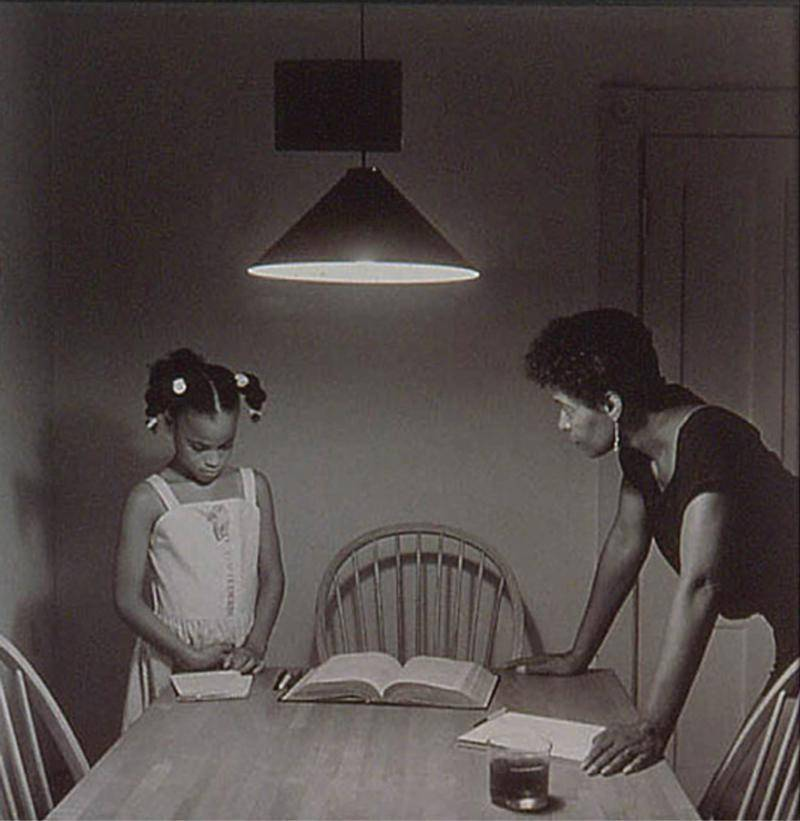 Black and white photoof an African American woman talking to her daughter at the kitchen table