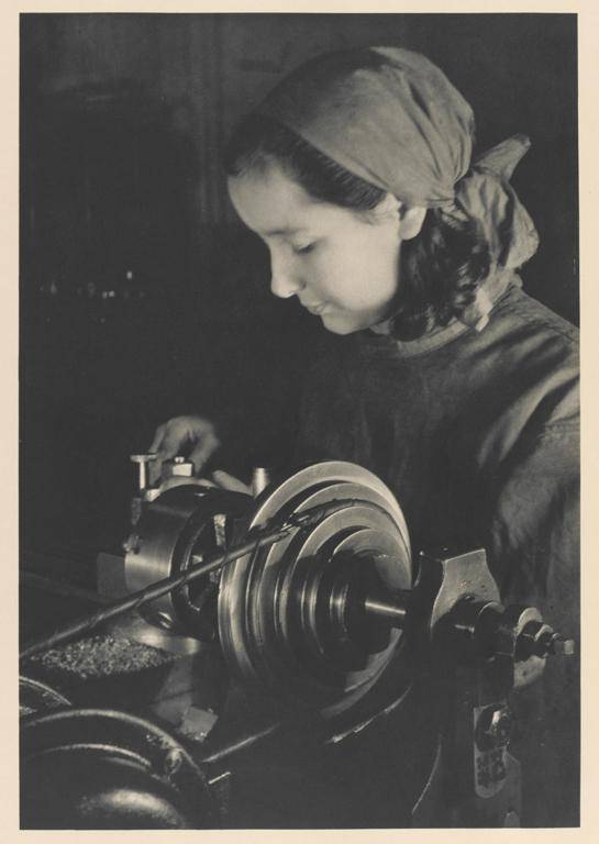 Black and white photograph of a woman working at a machine