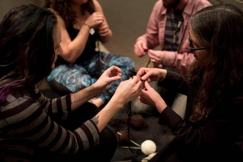 Visitors crocheting chains out of different fiber with artist Viviane Le Courtois inside the Global Thinking Pod