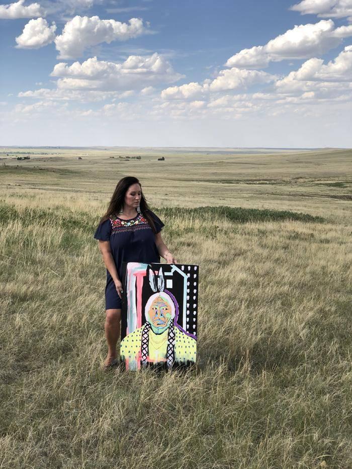 Danielle SeeWalker outside on the prairie standing next to her painting of Sitting Bull