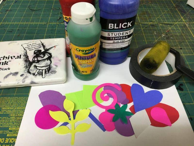 Supplies laid out- tempera paint, foam roller, cut out shapes, tape, and blank paper.