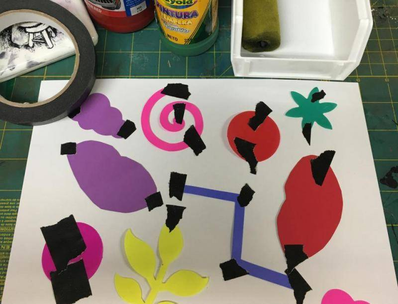 Tape is used to attach a variety of shapes to the blank sheet of paper.