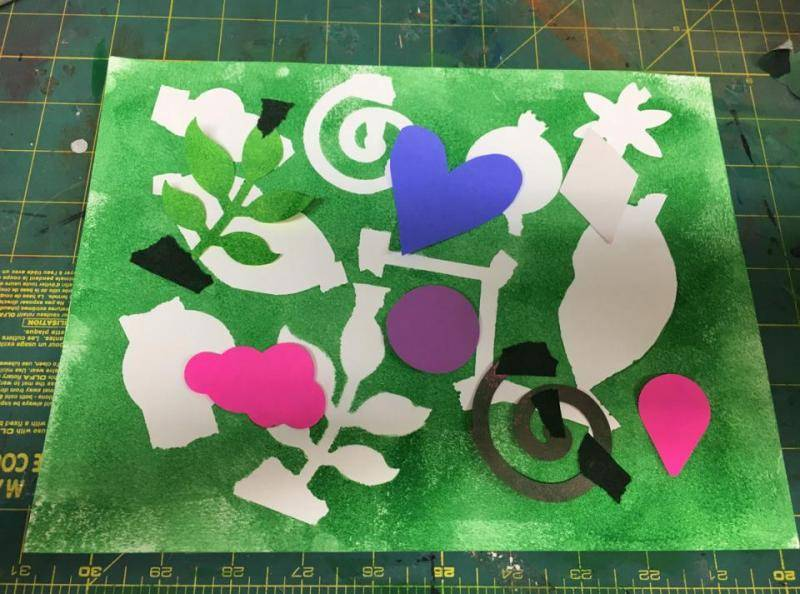 More shapes are taped onto the surface and layered on the negative space.