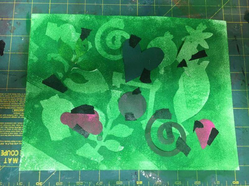 Green paint is rolled over the second layer of taped down shapes.